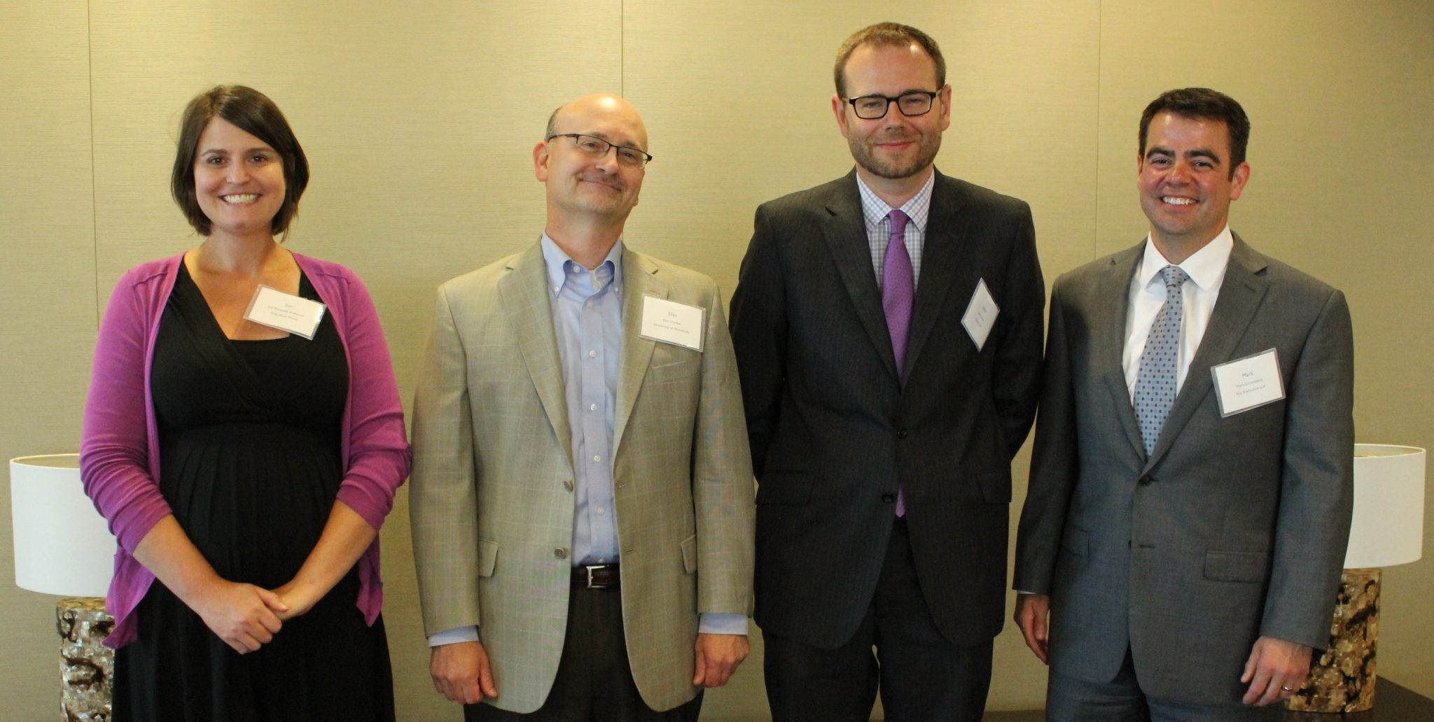 L to R photo interior of Joy Anderson, Dan Herber, Julian Zebot and Mark Schneebeck smiling in business attire