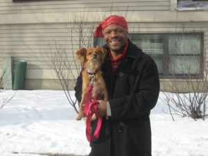 man with red bandanna on his head smiling and holding a dog in winter in front of a tan house