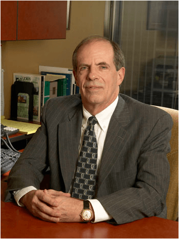 attorney steve rathke sitting at a desk in a dark gray suit